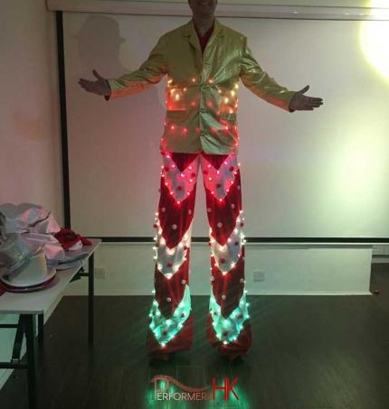 Stilt walker in Hong Kong lighting up his LED candy cane costume for photo