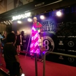 Led stilt walker standing outside nightclub in Hong Kong with model