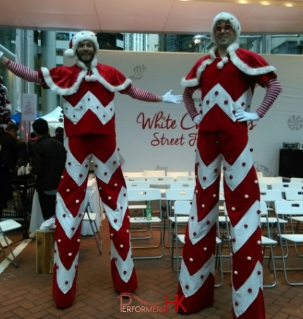 Two candy cane looking stilt walkers standing next to Swire stage