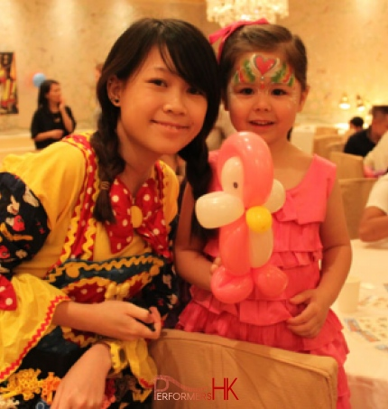 Hong Kong walk around balloon twister dress as a clown with a Mickey Mouse clown costume taking picture with a little girl wearing pink ,holding a pink Pingu at a Children birthday party
