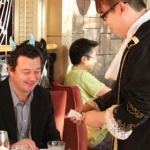 Joker performing strolling magic to a patron at a french themed event in Hong Kong.
