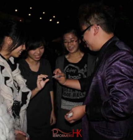 Hong Kong magician performing roving magic to four girls standing