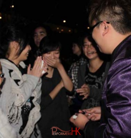 Magician performing roving magic to four girls at a Hong Kong Bank corporate cocktail event.