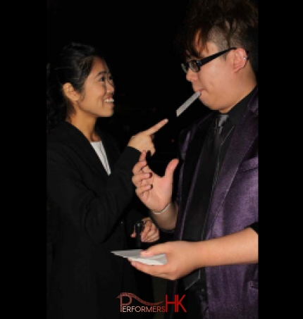 A Hong Kong Ladies was impressed and pointing a card with her signature which the roving magician picked up and holding it with his mouth at a corporate cocktails party
