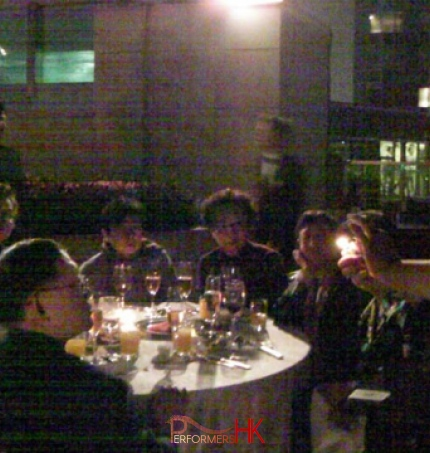 Magician in HK performing roving fire magic in front of a table of guests at a corporate dinner event