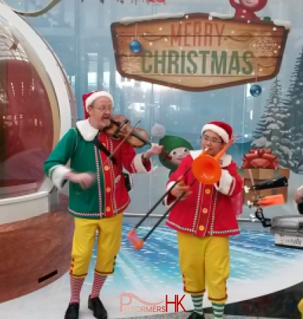 Xmas band trio playing with santa sitting in giant snow globe in background.