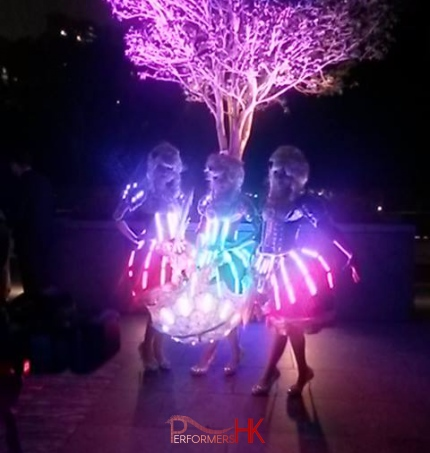 The LED dancers donning period dresses standing under lit up tree