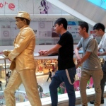 Golden statue performer having fun with visitors at the APM mall Kwun Tong, Hong Kong.