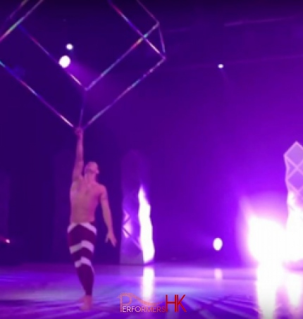 Acrobat spinning a giant steel cube above his head