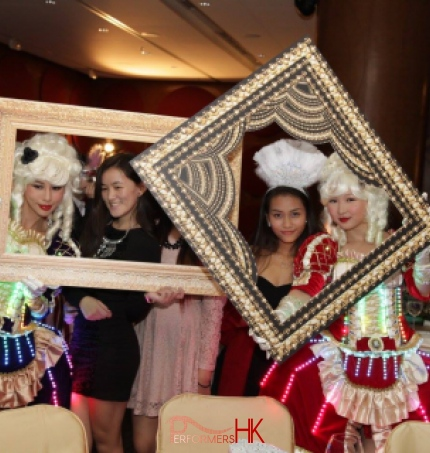 Two pretty girls wearing courtesan style costume with LEDs and having pictures taken with large photos frames