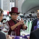 Magician in purple suit with a purple top hat performing table magic to four gentlemen at Hong Kong Happy Valley Races