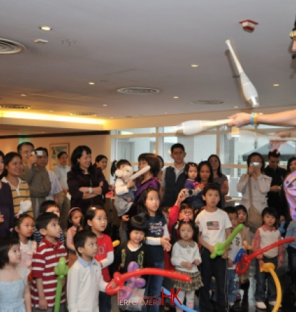 Juggler in HK performing unicycle with 3 cups at a Children event