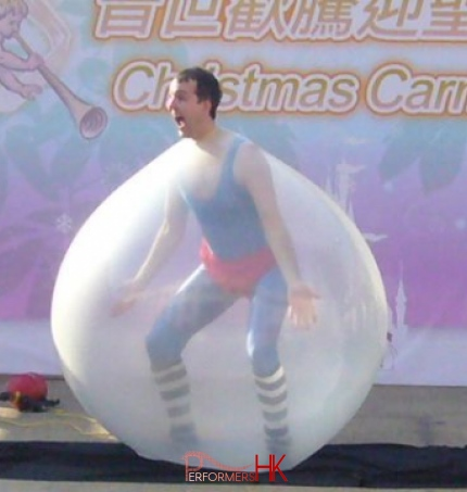 Juggler performing his famous trick , getting inside the giant balloon act at a Hong Kong Christmas Carnival
