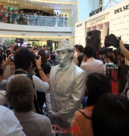 Silver man human statue standing in a crowd with lots of photographs being taken
