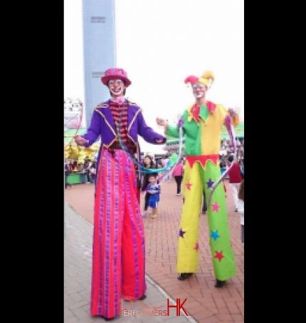 Two stilt walkers performing poi tricks