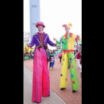 Two stilt walkers performing poi tricks