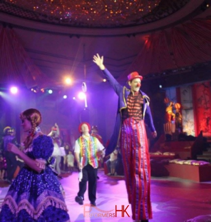 Stiltwalker and juggler and pretty girl in parade in the Hyat Hong Kong ballroom