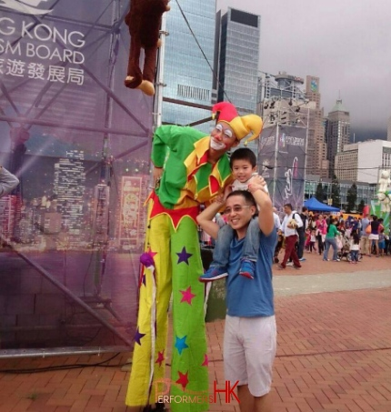 Stiltwalk wearing jester costume taking photo with dad with child on shoulders