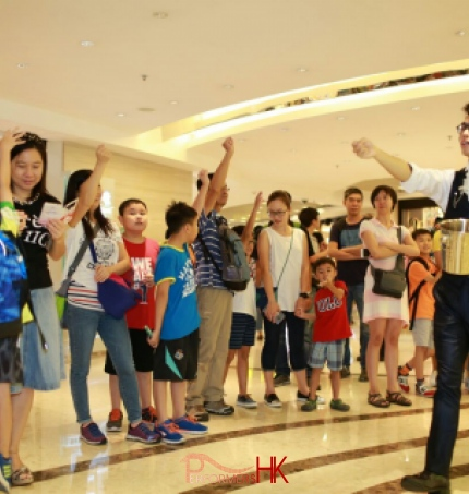 Roving magician performing coins magic at a corporate shopping mall event in Hong Kong