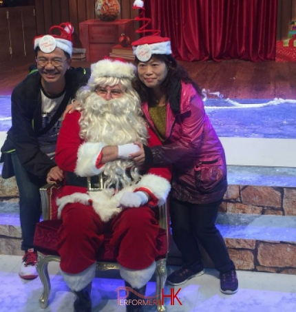 HK performer dress as Santa, taking picture with two tourists who wearing Xmas hat in front of the Xmas backdrop at a Hong Kong Christmas function.