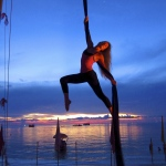 Female aerial sills performer shows her flexibility and grace under the sunset.