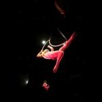 Female aerial performer manipulates her two hoops in midair.