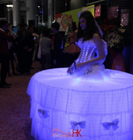 Model dressed in LEd lights and standing in the middle of a table