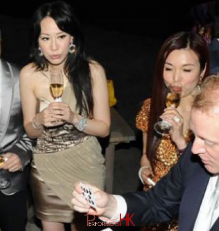 Magician performing table magic in front of the famous Hong Kong Kung Fu movie star and his model wife at a cocktails party