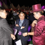 Walk-around magician performing to two gentlemen at a race meet in Hong Kong