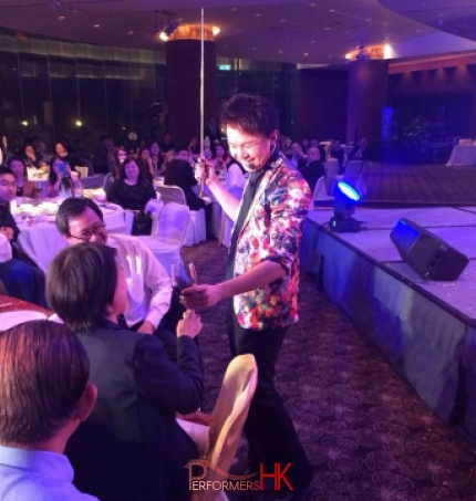 Roving magician in Hong Kong performing roving magic to CEO with wine at annual dinner