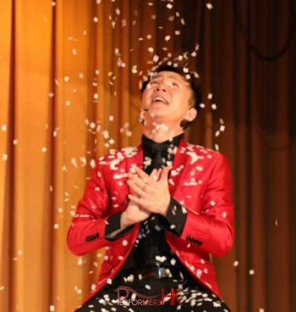 Hong Kong Magician wearing a red jacket performing snow storm magic trick at a corporate annual dinner