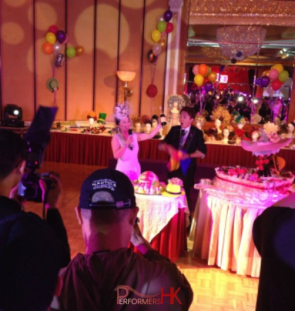 Hong Kong Magician performing roving magic with the birthday lady who holding a bottle of wine at a hat theme adult birthday party