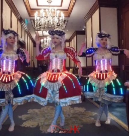 Three dancers wearing victorian era dresses with LED lights