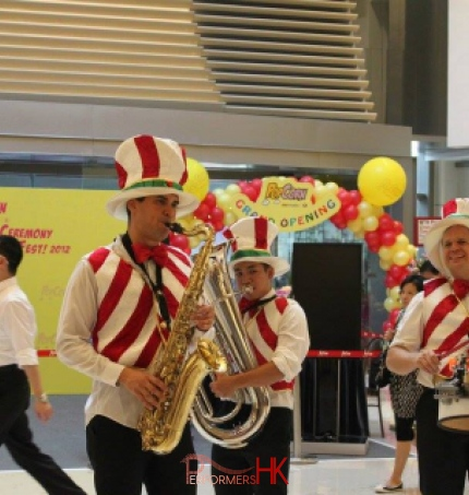 Three strolling musicians wearing colorful candy cane vests in a mall