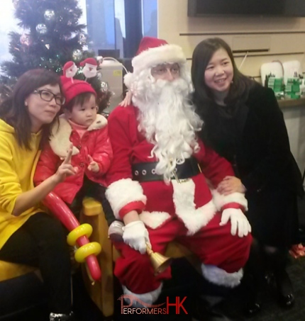 Santa with two ladies and a baby sitting in front of a Christmas tree at a Kong Kong corporate event.