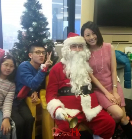 Santa with a lady and two kids taking picture in front of a Christmas tree at a HK Xmas event