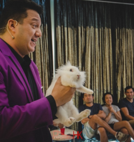 Hong Kong Magician in purple suit performing magic with a live bunny at a corporate event