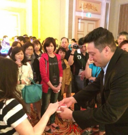 Walk around magician performing close up card magic and invited a guest to pick a card at a cocktails party in Hong Kong
