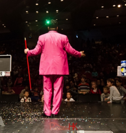 Children looking at the magician in Hong Kong who holding a red wand , standing next to the magic case , performing at the corporate kids event