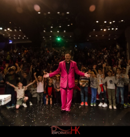 Hong Kong stage magician taking a picture with his audience after his performance at a corporate children event