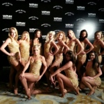 Dancers in gold dresses posing in front of backdrop at Ritz Carlton hotel event.