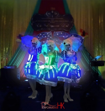 Three dancers in period costume with LED lights and umbrellas