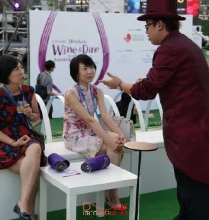 Roving magician at an exhibition in Hong Kong preforming a card trick to two girls