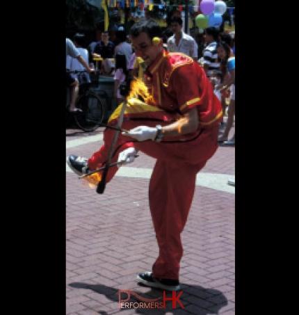 Hong Kong juggler juggling Fire Devil stick under his leg at a corporate event