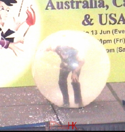 Hong Kong talented clown climbing inside a giant balloon at a shopping mall event.He is the only one to do this act in HK
