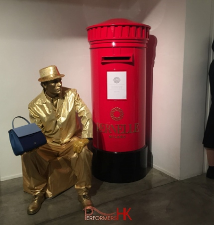 Living Statue holding handbag sitting next to red post box in hong kong