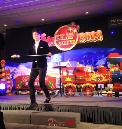Magician performing stage magic with rope in front of a train backdrop at Hong Kong Swiss Privilege Christmas Dinner