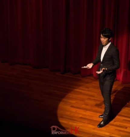 Hong Kong Magician performing stage magic with a spotlight on him at corporate annual dinner