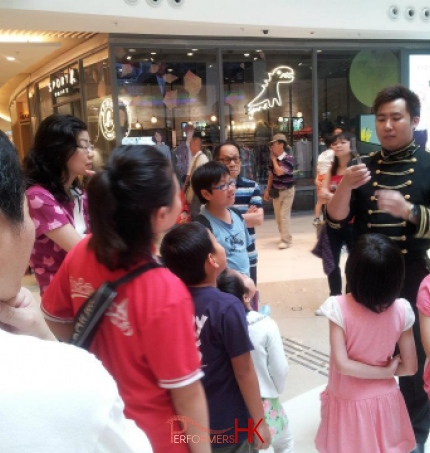Roving Magician performing spoon bending magic to children at Hong Kong Popcorn Mall store opening event