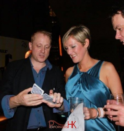 Magician playing with cards to two guests holding drinks